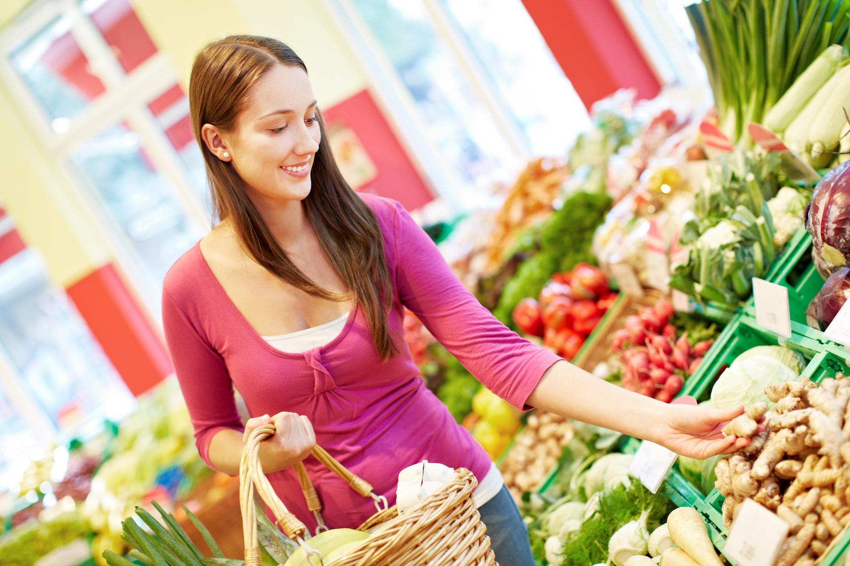 Junge Frau kauft Gemüse in einem Bio-Supermarkt